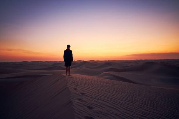 Lonely man in the middle of desert Lonely man standing on sand dune in the middle of desert at dusk. Abu Dhabi, United Arab Emirates horizon over land stock pictures, royalty-free photos & images