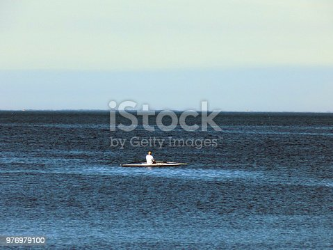 Lonely man in the rowboat in the middle of the sea