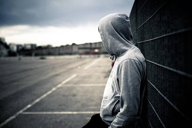 lonely mann auf einem zaun lehnend - jugendalter stock-fotos und bilder