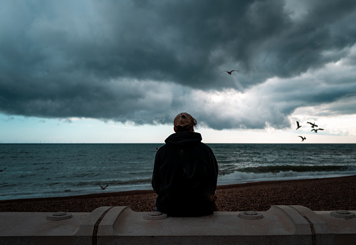 Rear view color image depicting a young man sitting alone at the beach, looking at the dark sea and storm clouds. Moody image emphasising loneliness and isolation. Seagulls are circling and swooping in the distance.