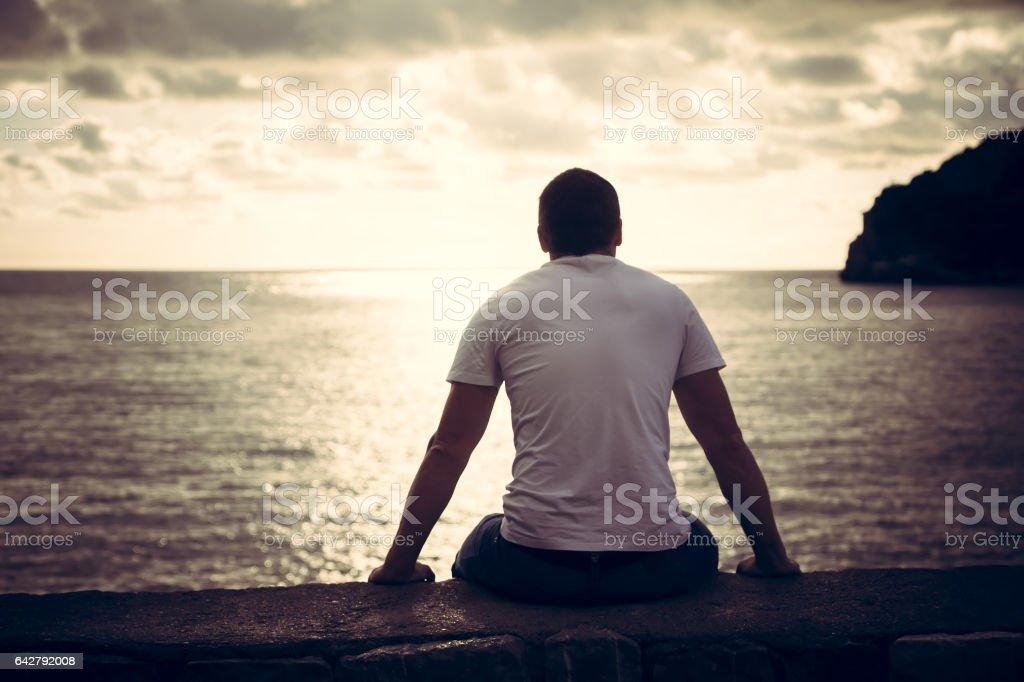 Hombre solitario mirando con esperanza en el horizonte con luz del sol durante el atardecer con el efecto de la luz al final del túnel - foto de stock