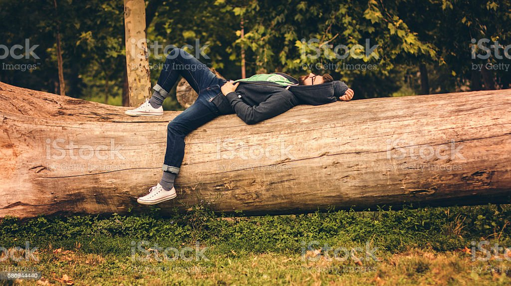 Lonely man lying on cutted tree in forest stock photo