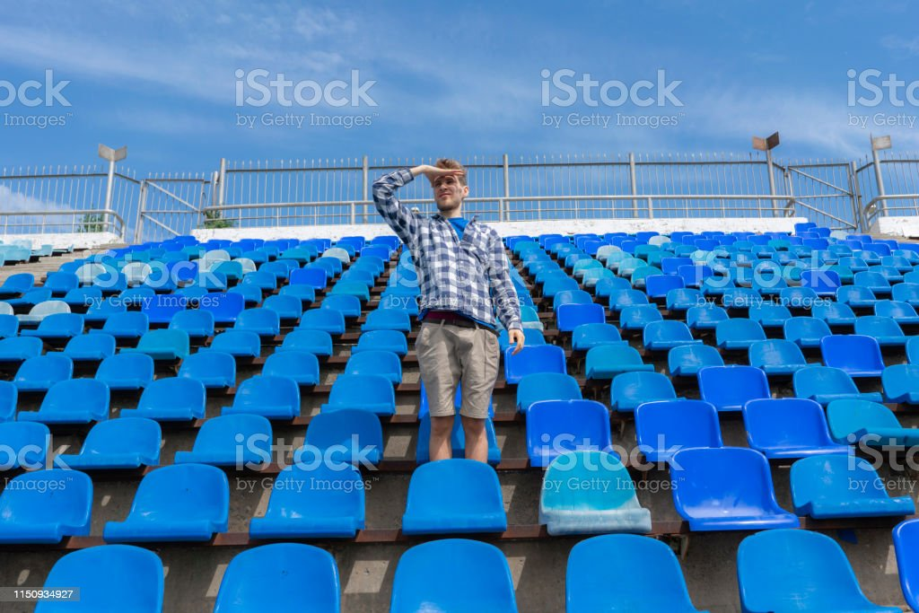 lonely man on the empty stadium seat cheering for the team, one man...
