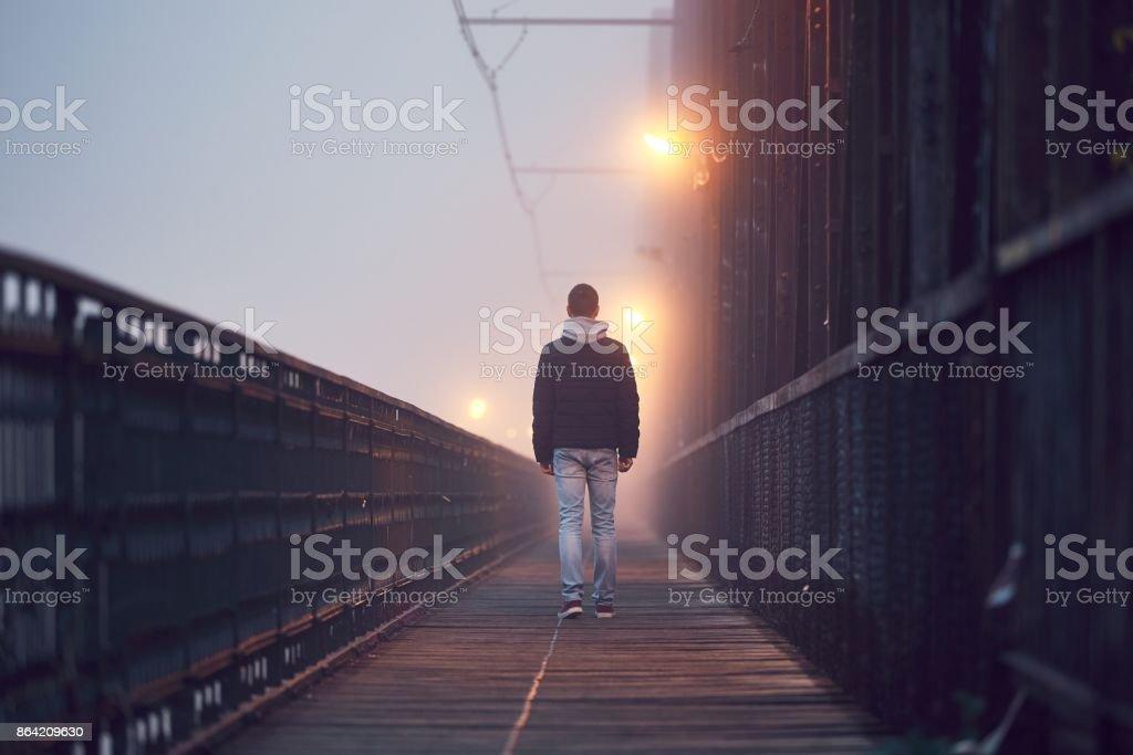 Lonely man on the old bridge stock photo