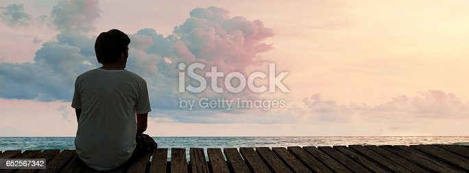 istock Lonely Man sitting in a wooden dock pier in sea beach with twilight sky in sunset time and think concentrate 652567342