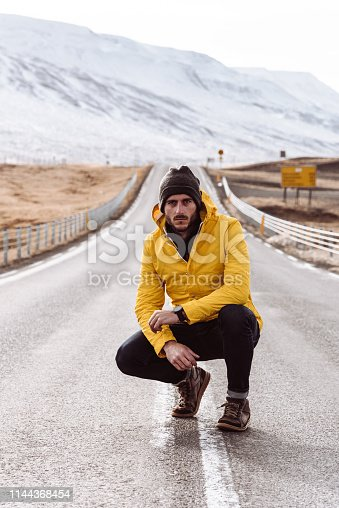 lonely man sitting in the middle of the road in iceland
