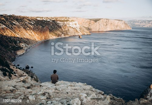 Lonely man sitting on cliff edge and watching on sea. Beautiful landscape. unity of man and nature concept.