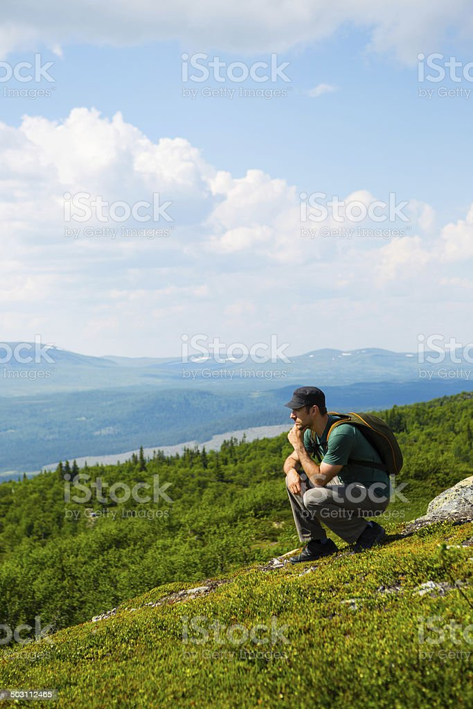 Lonely man sitting on mountain top royalty-free stock photo