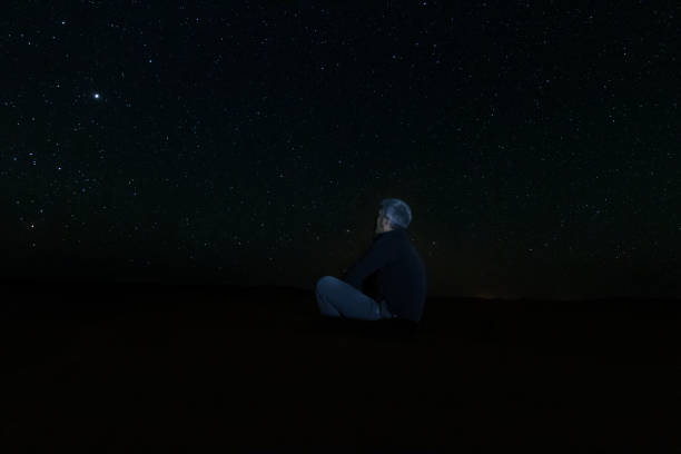 A lonely man sitting on the desert sand looking at the starry sky, between dunes in the desert of Erg Chebbi stock photo