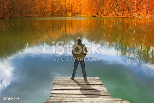 Lonely man standing on the edge of the small wooden pier looking at the lake and colorful forest on the other side
