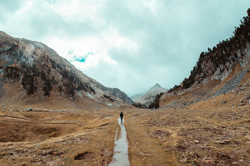 Lonely man walking in nature of Benasque Valley, surrounded by the highest peaks in that range, located in the heart of the Pyrenees, Aragón, Spain