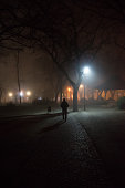 Lonely man walking home through the city park on misty winter night