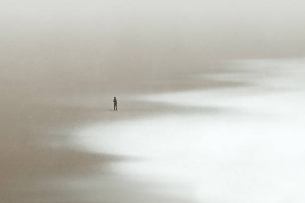 Lonely man walking in the sand looking at the calm sea, surreal minimal seascape stock photo