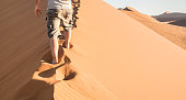 istock Lonely man walking on sand crest at Dune 45 in Sossusvlei desert - Wanderlust concept with hiker guy in namibian famous place - Adventure trip travel to african wonder in Namibia - Bright natural tone 872845932