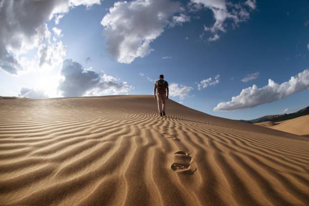 Lonely man walks in desert dunes