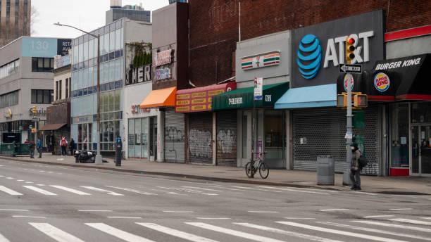 Einsamer Mann mit Schutzmaske, der in der Delancey Street in Chinatown vor den Läden steht, die wegen des COVID-19-Ausbruchs geschlossen sind – Foto