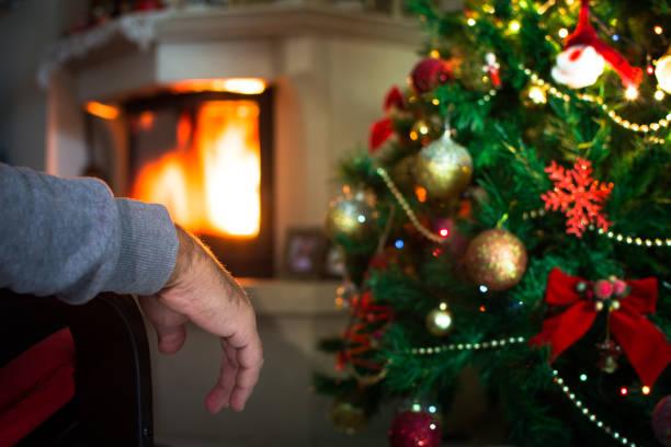 Einsamer Mann Hand vor dem Kamin mit Weihnachtsbaum. – Foto