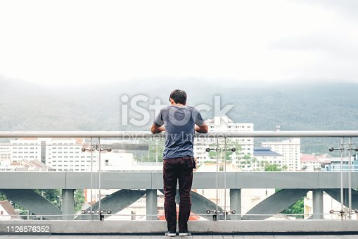 1127798356 istock photo Lonely men are looking city view and sunset 1126576352