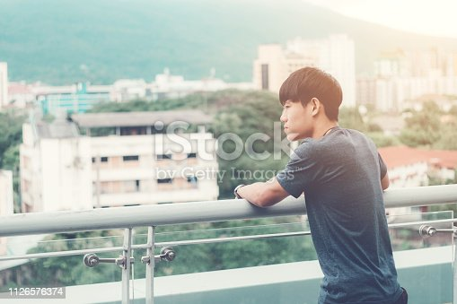 1127798356 istock photo Lonely men are looking city view and sunset 1126576374