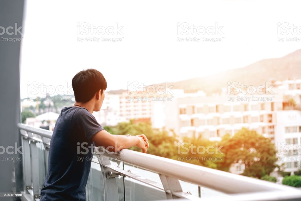 Lonely men are looking city view and sunset stock photo