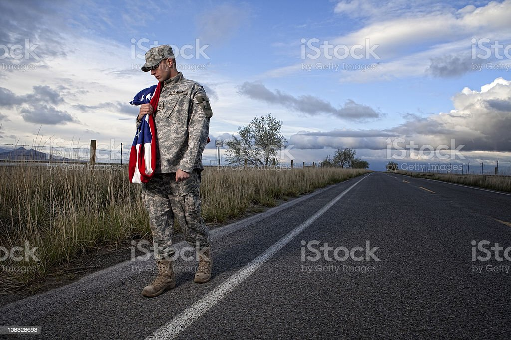 Lonely military soldier walking down a road royalty-free stock photo