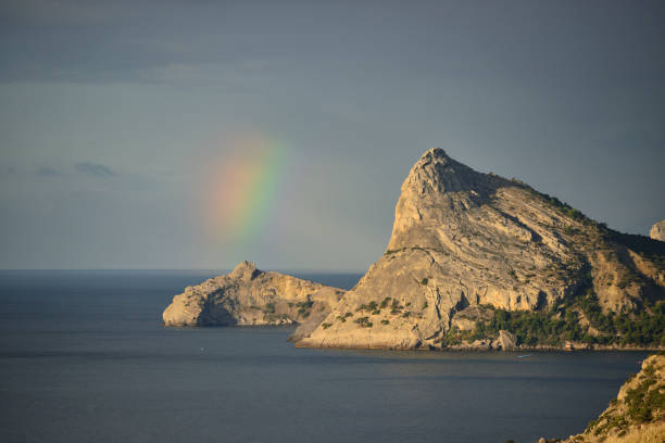 Cтоковое фото Lonely mountain against the blue sky and rainbow.