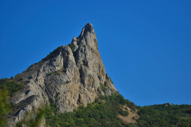 Cтоковое фото Lonely mountain Falcon on a background of blue sky