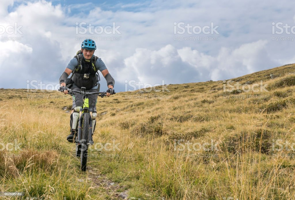 Lonely mountainbiker on a pasture in the Friulian Mountains, Italy. stock photo