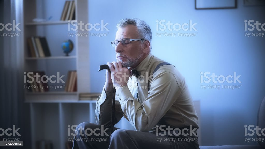 Lonely old man leaning on walking stick, dreaming, remembering youth,...