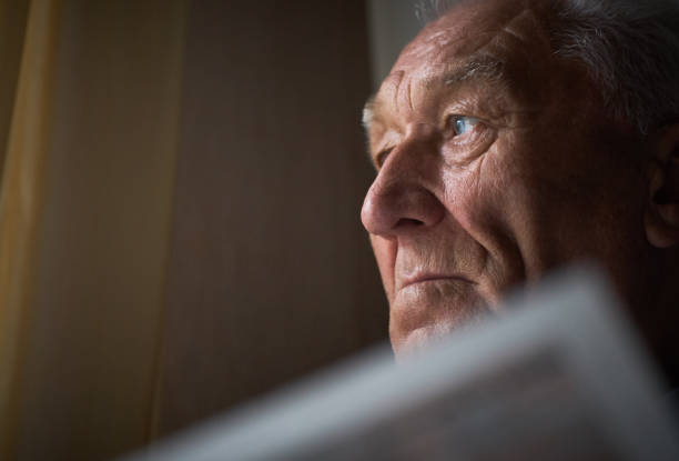 Lonely old man reads the world news in the newspaper. An elderly man reads the world news in the newspaper at home. Lonely old man holding a newspaper and he looks out the window. one senior man only stock pictures, royalty-free photos & images