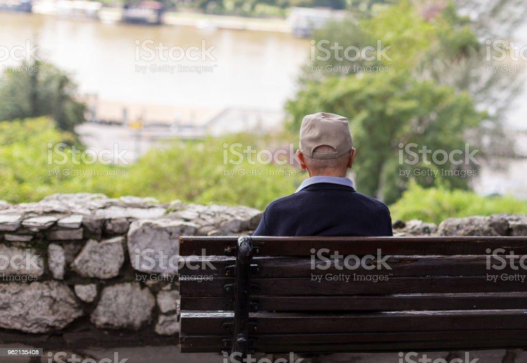 Ein einsamer Alter Mann sitzen auf einer Bank in einem Park, Blick auf Fluss – Foto
