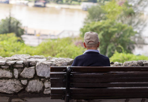 A lonely old man sitting on a bench in a park, looking at river stock photo