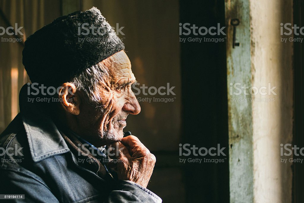 Lonely old man staring out of a window stock photo