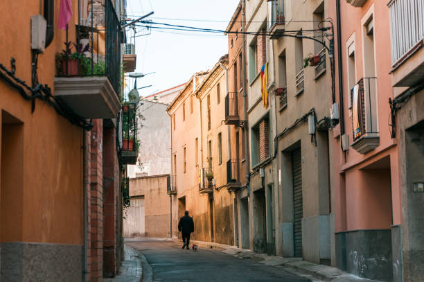 lonely old man with dog walk in street of small catalan spanish medieval town during sunny spring day stock photo