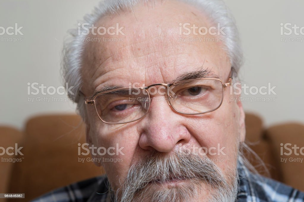 A lonely sick poor old man suffering from eye diseases, independently...