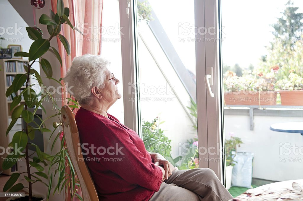 lonely old woman lonely old woman looks out the window 70-79 Years Stock Photo