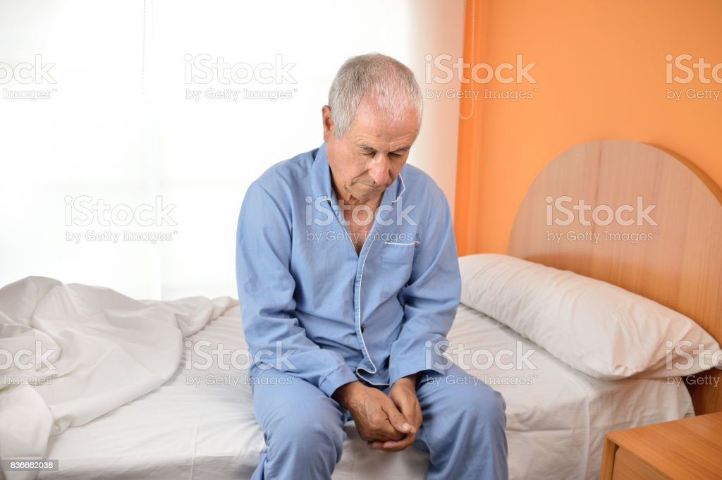 Senior man sitting on bed with his hands on knees