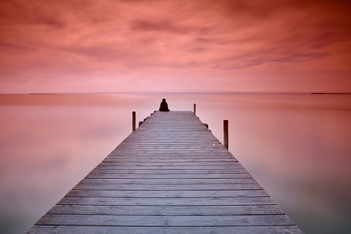 Lonely person sitting on pier