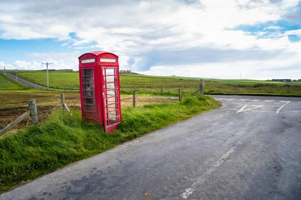Einsame rote Telefonzelle am Straßenrand in der Nähe einer Straßenkreuzung auf dem Land – Foto