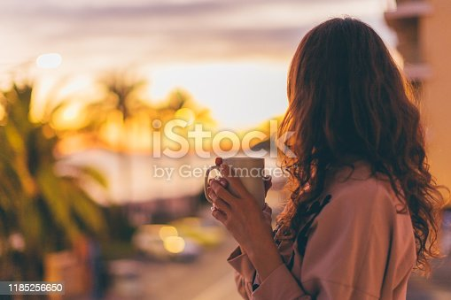 Rear view of a girl with cup of hot drink
