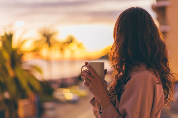 Lonely romantic girl drinking coffee looking at sunset.