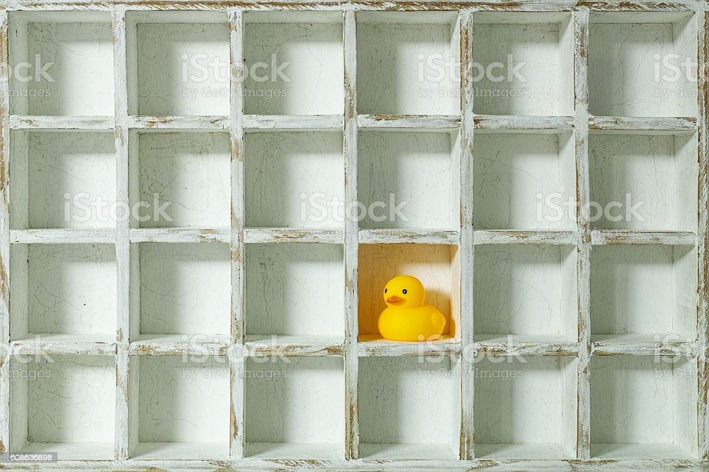 Lonely rubber duck in a compartment of many pigeon hole. stock photo