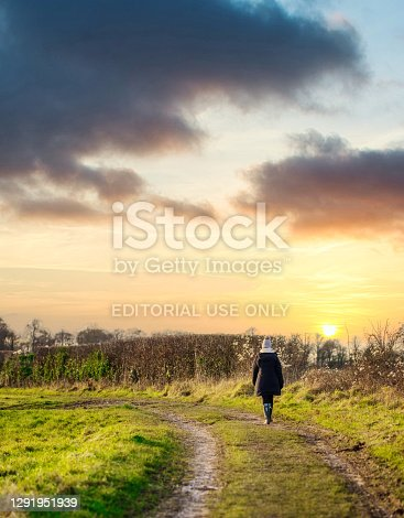 Lonely sad woman walking along a long an endless muddy farm track vanishing into the distant horizon in the Cotswold landscape as she reflects on life.