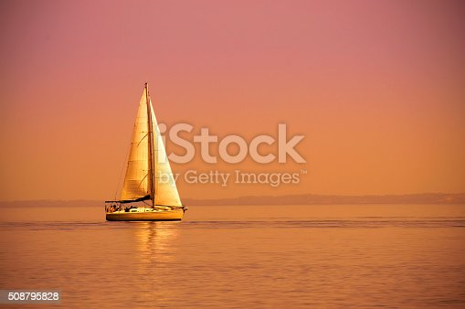 Lonely sail boat at sunset