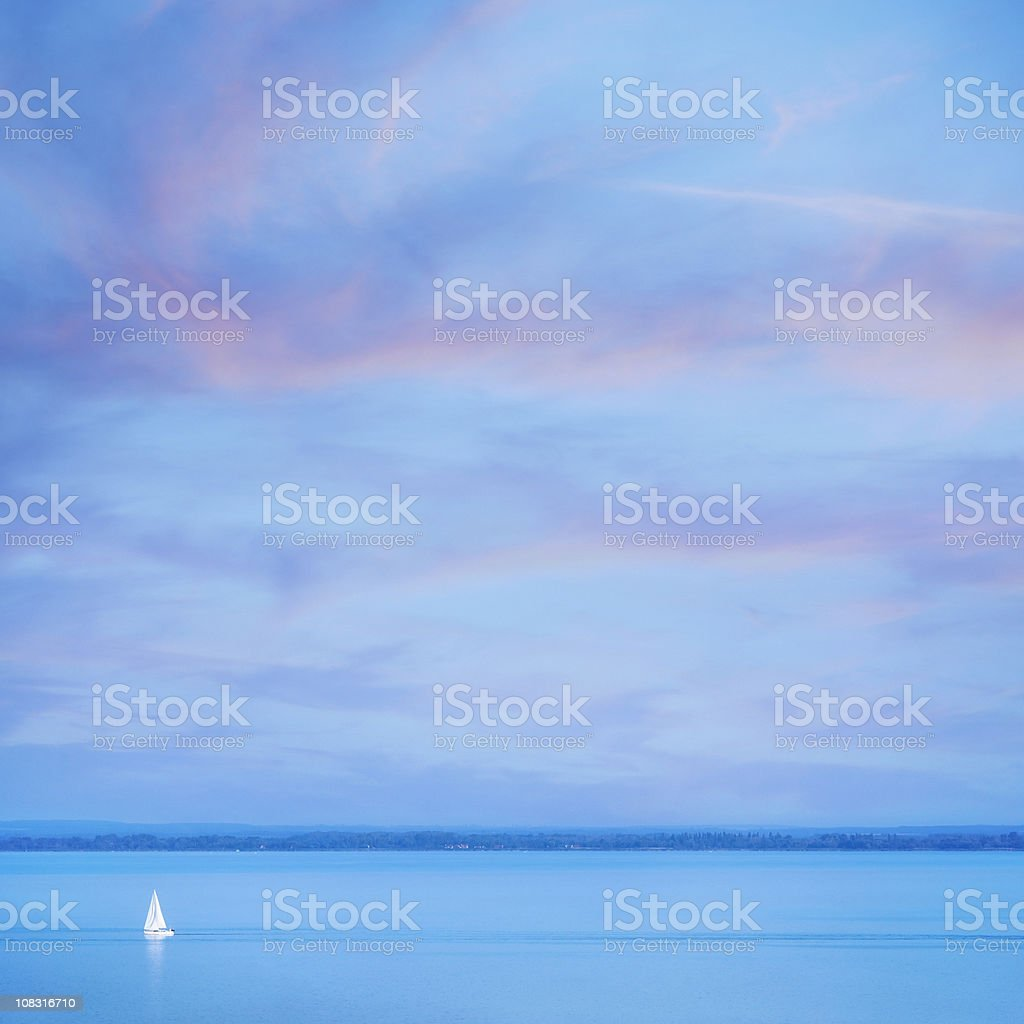 Lonely sailboat at twilight stock photo