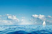 Blue sea with white sailboat on the horizon.