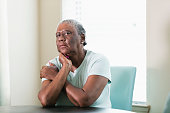 A lonely senior African-American woman in her 70s sitting at home at a table by a window. She is looking at the camera with a serious expression, elbows on the table and head leaning on her hand.
