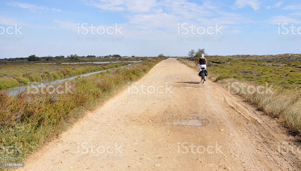 Lonely senior female cyclist in the french Camargue. stock photo
