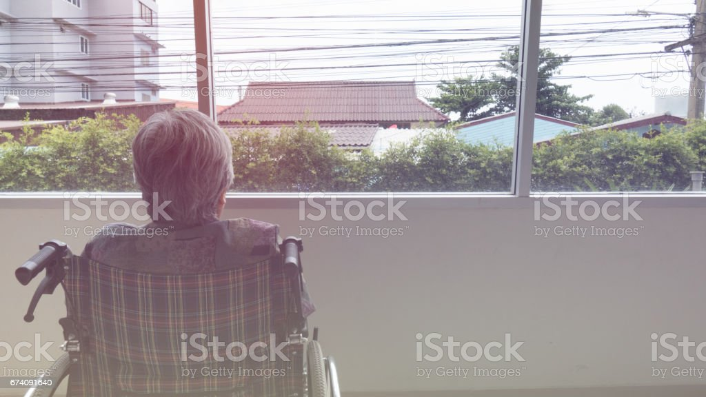 lonely senior looking through window in building - age, loneliness and people concept royalty-free stock photo