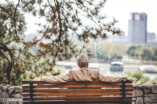 Lonely senior men is sitting on a bench in a public park. He is looking at distance